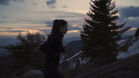 Determined female runner aimed to reach mountain top. Sunset sky in bright Live Action