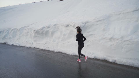 Lonely jogger with bright pink running shoes sprinting in snow corridor in Live Action