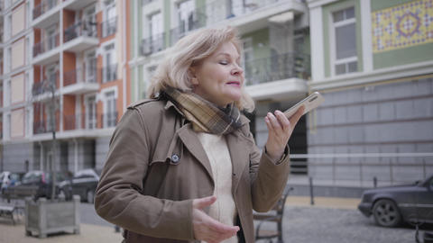 Portrait of mature elegant Caucasian woman walking on city street and talking on Live Action