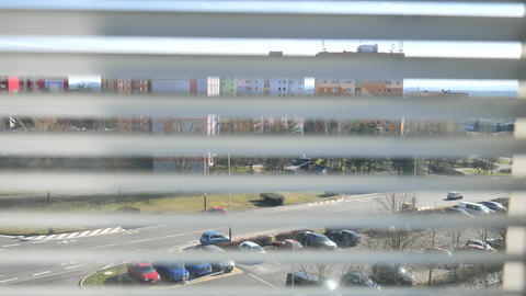 Window view through the blinds at the street through the blinds. Town street through silver window Live Action
