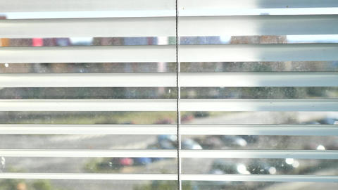 Town street through silver window blinds. Movement on street between flat houses through window open Live Action