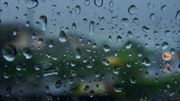 Tracking video of rain drops on train window and blurred city with moving cars Footage