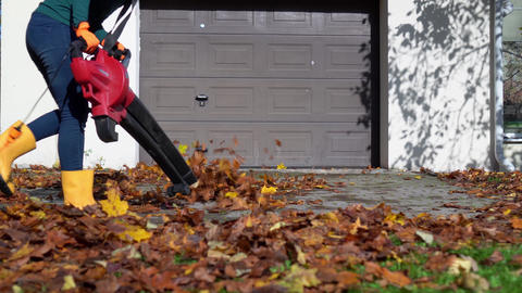 Mad playful woman with leaf blower have fun near garage Live Action