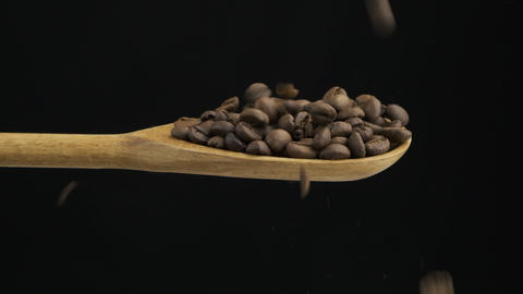 Falling bean coffee fills the spoon and fall out of a wooden spoon. Slow motion Live Action