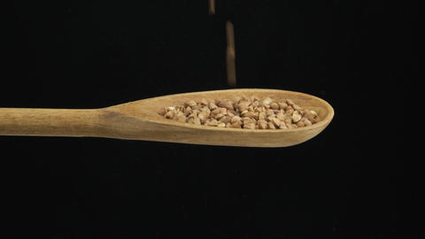 Falling grain buckwheat fills the spoon and fall out of a wooden spoon. Slow Live Action