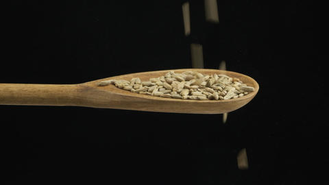 Falling grain rye fills the spoon and fall out of a wooden spoon. Slow motion Live Action