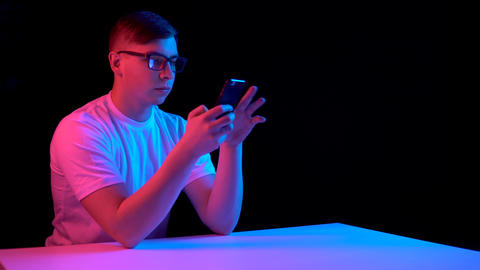 Young man with a smartphone. A man is using a telephone. Blue and red light Live Action