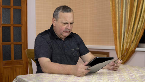A man uses a tablet for the first time. An old man is having difficulty using a Live Action