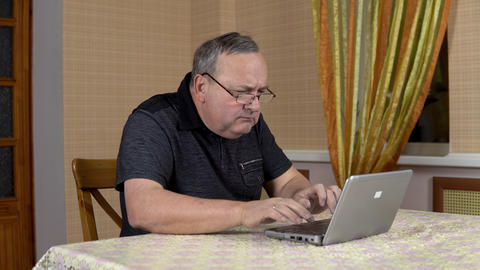 Man is using a laptop for the first time. The old man hardly uses a laptop hard Live Action