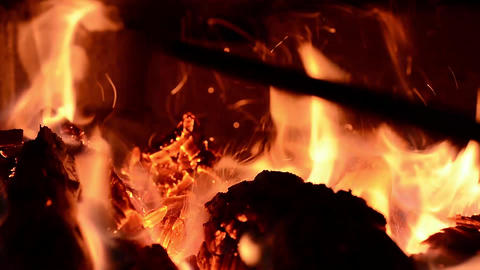 The fireman stirs a firewood in a stove, creating bright sparks and blowing fire Live Action