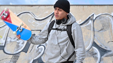 Young latin skater man posing with skateboard at skate park Live Action