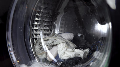 The washing machine is working. A washing machine spins a drum filled with Live Action