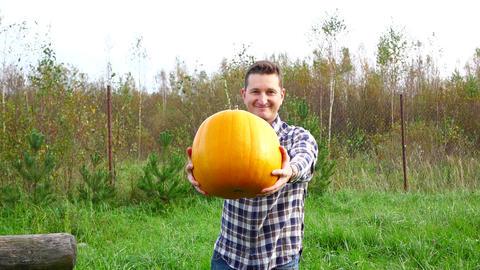 Portrait of curious smiling farmer reach out big orange pumpkin, slow motion Footage