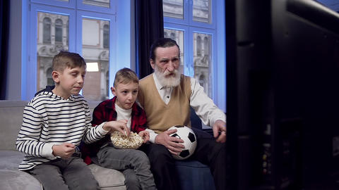 Close up of concentrated exciting two boys and mature bearded grandfather which Live Action