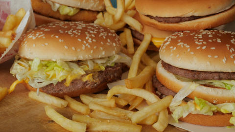 portion of unhealthy food, fast food, stack of burgers, fries rotating, turning Live Action