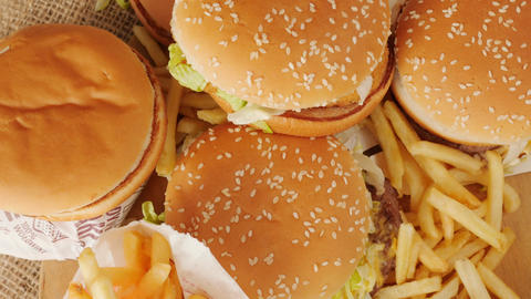 portion of unhealthy food, fast food, stack of burgers, fries rotating, top view Live Action