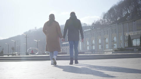 Camera following young man and woman strolling on city square on sunny autumn Live Action