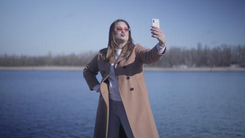Portrait of positive young woman sending air kiss and grimacing at selfie camera Live Action