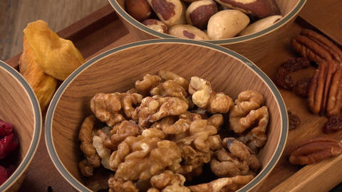 Mixed nuts and dried fruits in wooden bowl on wood background, copy space Live Action