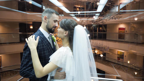 Bearded groom in a suit kisses his pretty bride in a wedding dress, riding in a Live Action