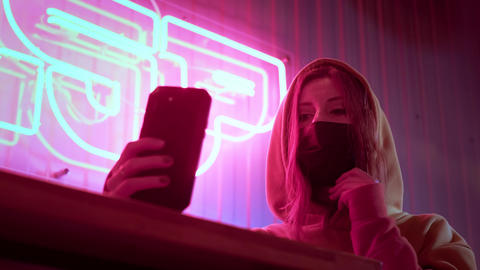 Young beautiful fashionable girl takes a selfie in black medical mask. In a bar Live Action