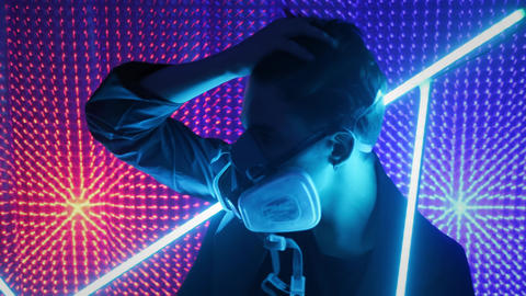 A model guy is dancing in a neon studio in a gas mask. Concept in dubstep style Live Action