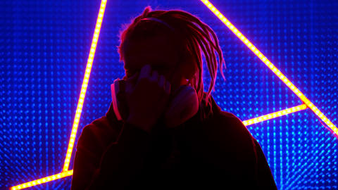 Young guy model with dreadlocks in neon lights. Neon triangle in a club studio Live Action