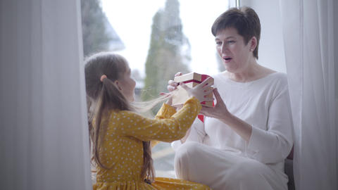 Portrait of surprised adult Caucasian woman receiving gift from cheerful little Live Action
