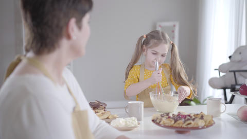 Serious little girl beating ingredients in bowl and smiling to blurred woman at Live Action