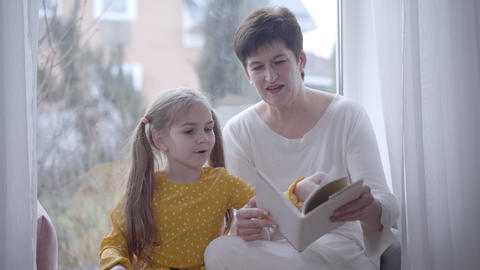 Portrait of confident adult woman reading book for granddaughter indoors Live Action