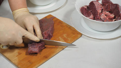 Cutting of meat of wild elk. Dark raw meat processing. Cutting on a wooden cutting Board Live Action