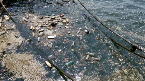 plastic bottles, bags, wastes floating in water. Sea ocean water pollution concept. Plastic Live Action