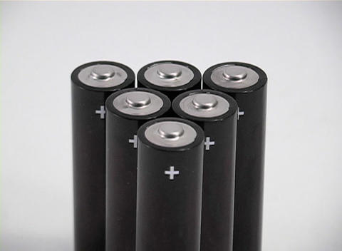 A closeup over a cluster of small batteries with plus signs Footage