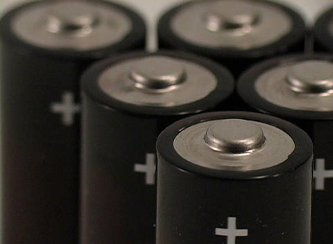 An extreme closeup over a cluster of small batteries with plus signs Footage