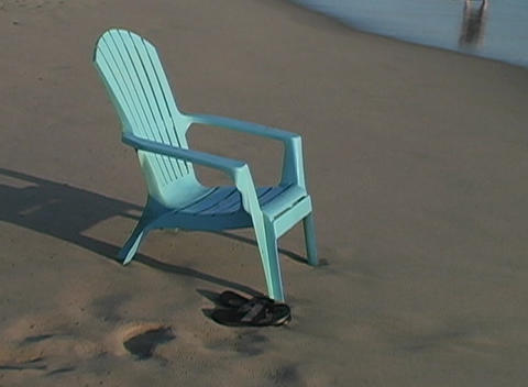 A deck chair sits on the beach as the waves roll in... Stock Video Footage