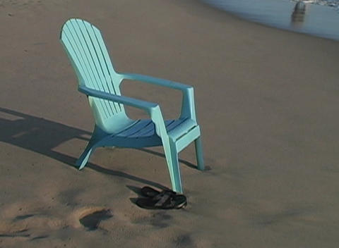 A deck chair sits on the beach as the waves roll in suggesting a relaxing vacation Footage