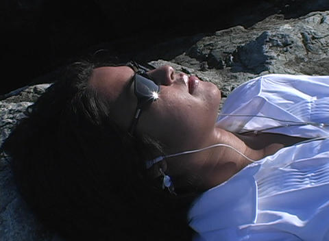 A woman with dark glasses lies in the sun listening to... Stock Video Footage