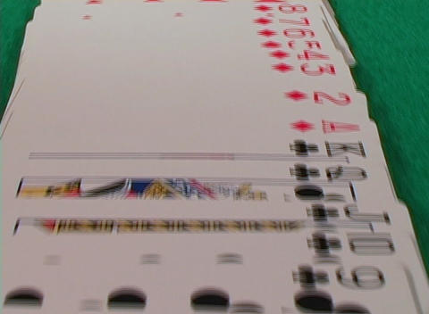 A flyover shot of a full deck of cards on a green felt table Footage