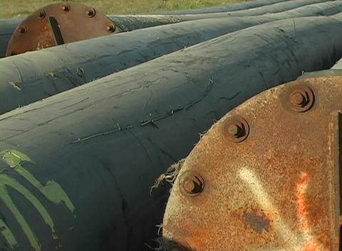 Oil pipes and metal fittings lie abandoned in a field Stock Video Footage