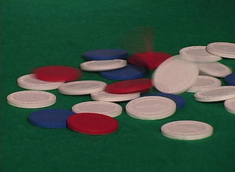 Poker chips tumble onto a green felt table in a casino Stock Video Footage