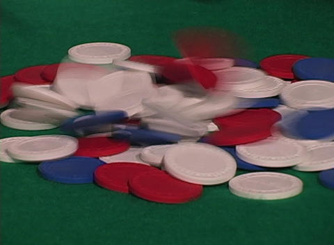 Poker chips tumble onto a green felt table in a casino Footage