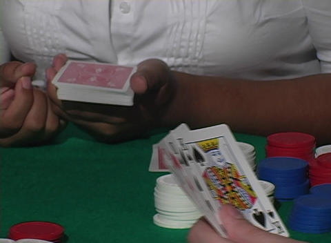 A dolly around a poker game reveals player's cards Footage