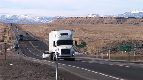 A semi- truck moves along a highway through the Rocky Mountains Footage