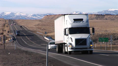 A semi- truck moves along a highway through the Rocky... Stock Video Footage