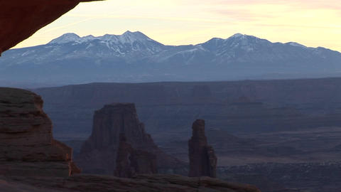 Snow-covered mountains with dramatic mesas in the foreground at Canyonlands National Park Footage