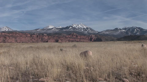 Snow-capped mountains rise above grassy plains of the American Southwest desert Footage