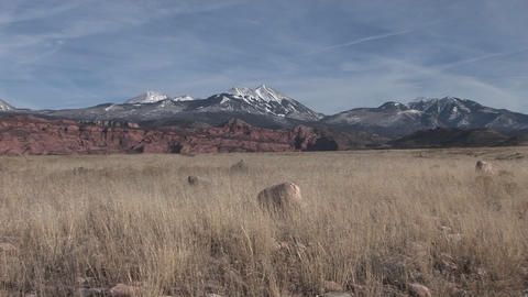 Snow-capped mountains rise above grassy plains of the... Stock Video Footage