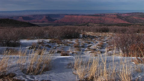 The desert southwest with distant buttes and snow in the foreground Footage