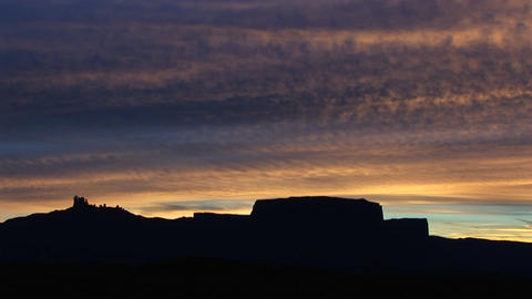 A horizon of desert buttes and rock formations is silhouetted at golden-hour in the American Southwe Footage