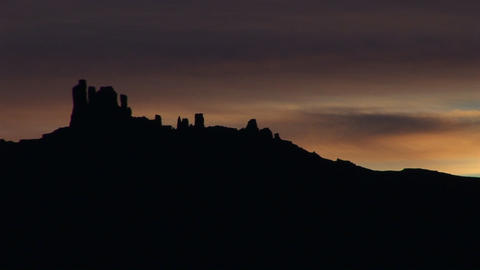 A horizon of desert buttes and rock formations is silhouetted during the golden-hour Footage
